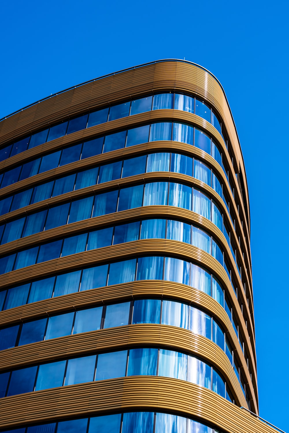 brown and blue glass building under blue sky