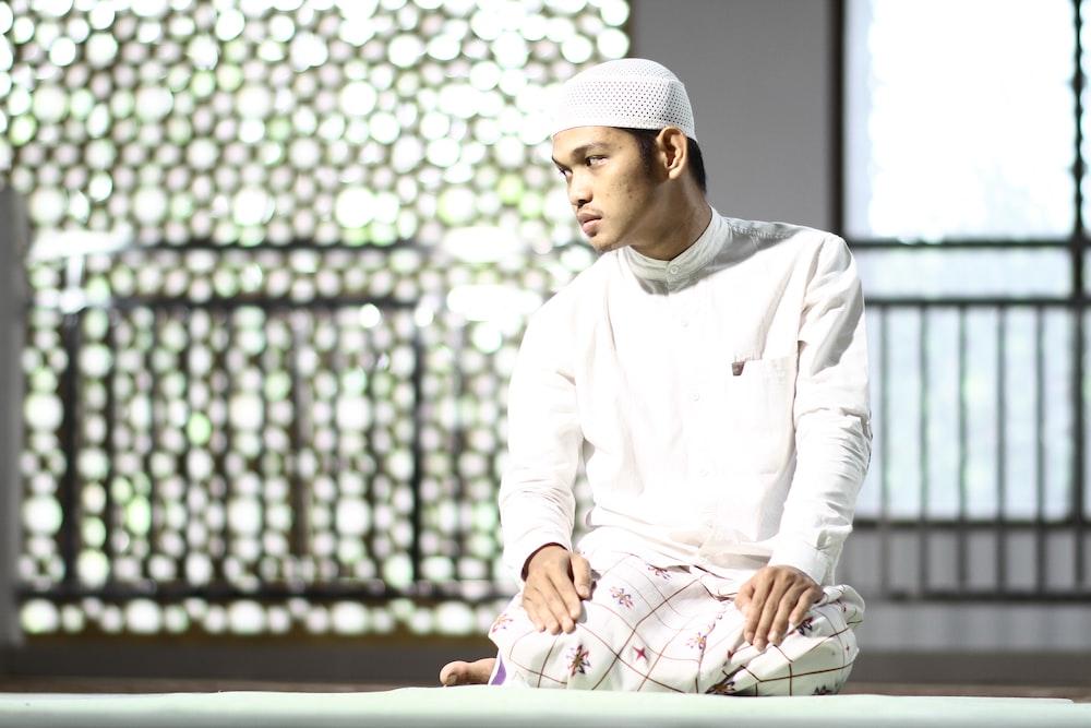 man in white thawb kneeling on floor