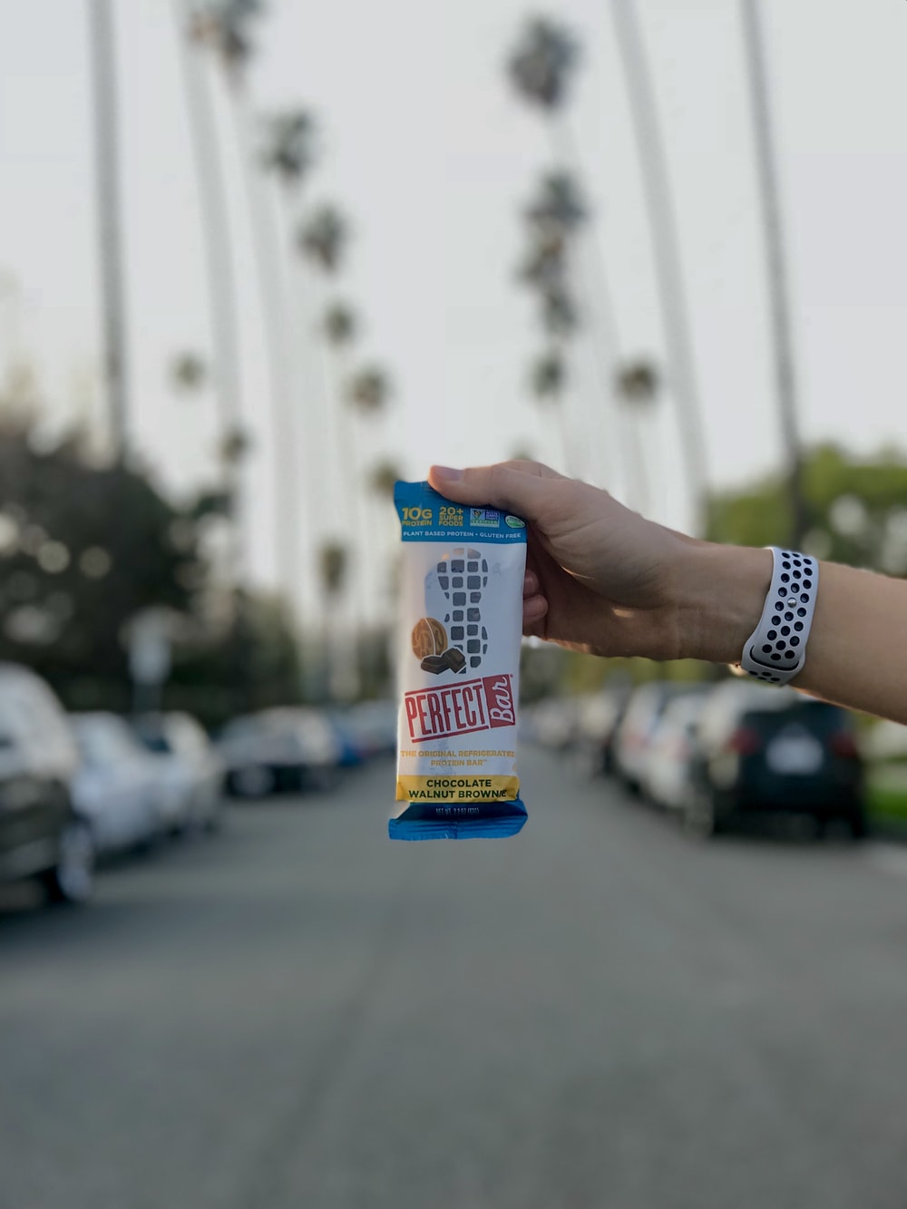 person holding white and blue labeled pack
