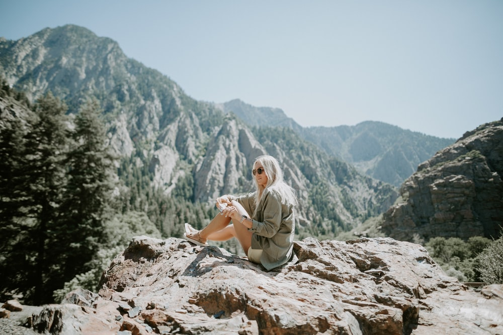 woman sitting on rocky hill viewing mountain under blue skies
