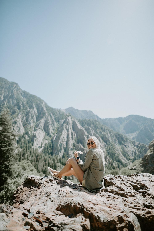 woman wearing grey blouse sitting on rock during daytime