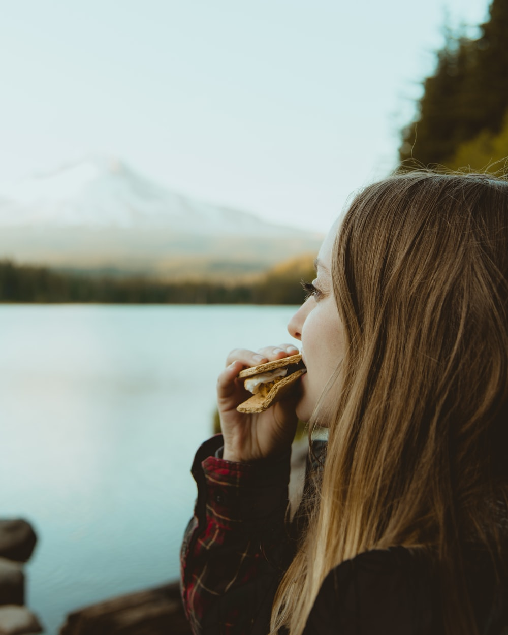 woman standing and eating food facing body of water viewing mountain