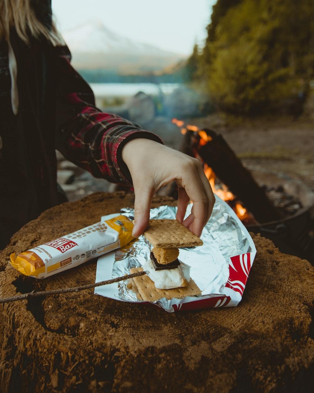 person making a biscuit sandwich near bonfire