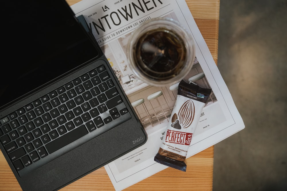 grey tablet computer with keyboard near cup and chocolate pack on table