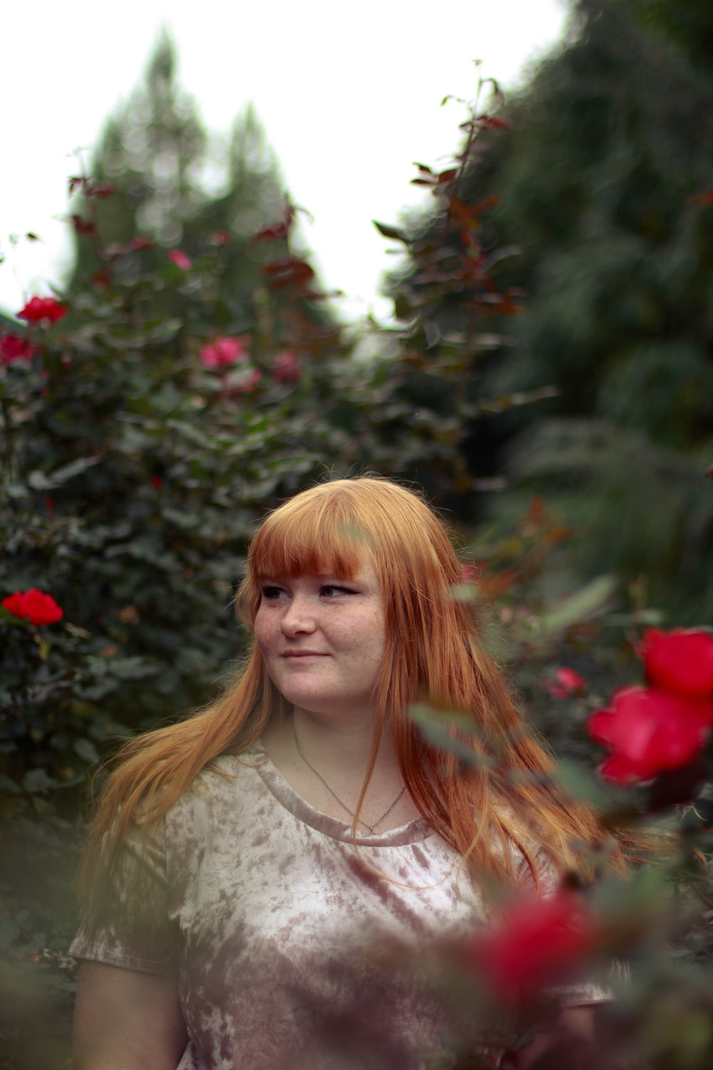 woman looking at her right beside red flowers