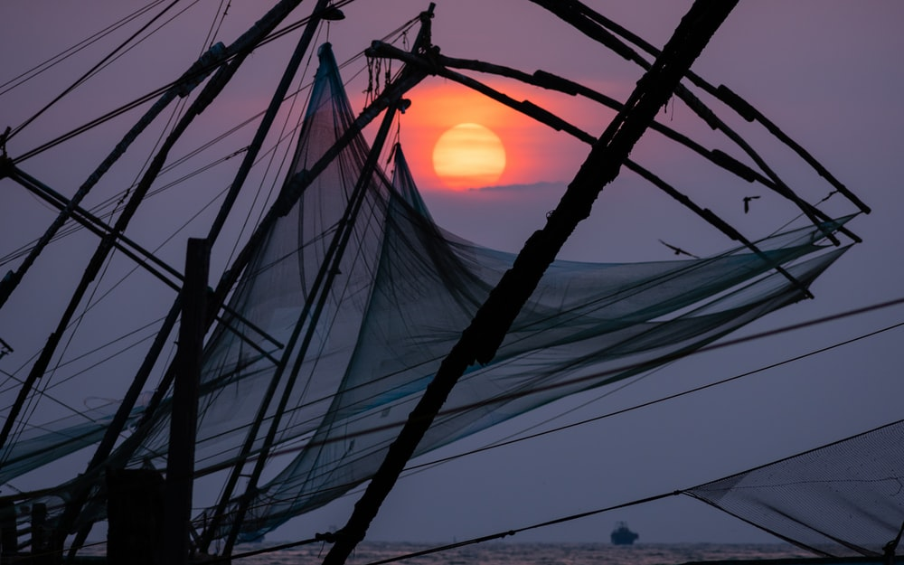 black sailing boat under sunset