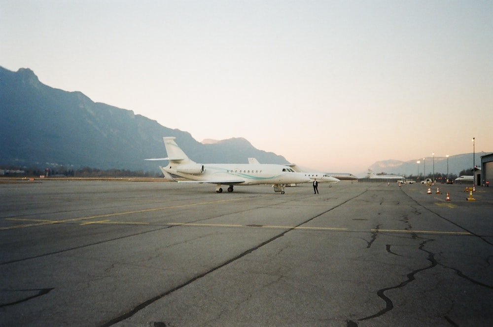 white airplane parked near mountains during daytime