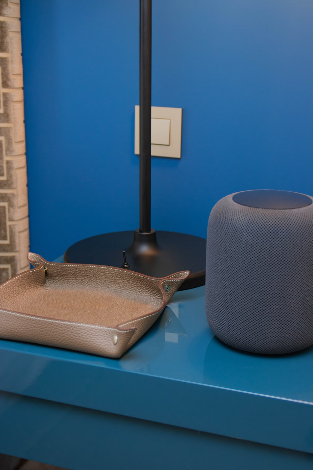 brown leather tray beside gray portable speaker and black table lamp base