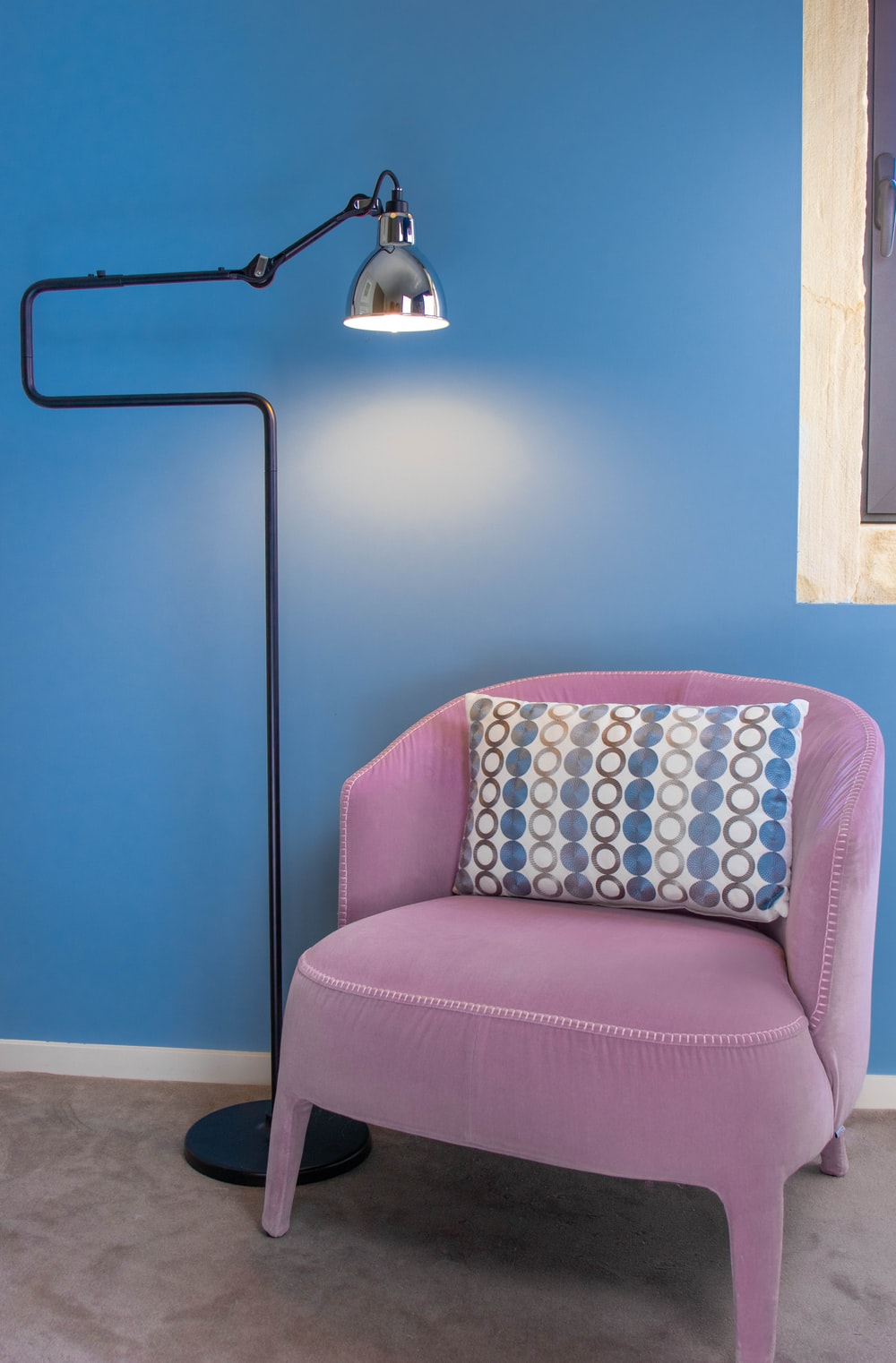 turned-on cantilever lamp beside sofa chair