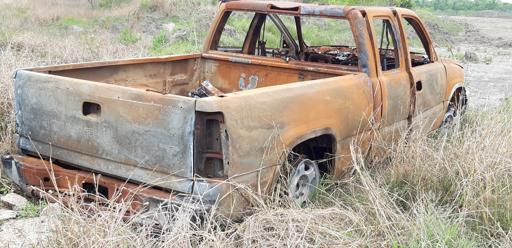 abandoned brown extra cab pickup truck on grass during day