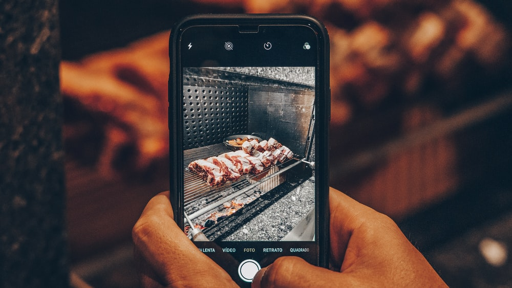 person showing photo o grilled meat on phone