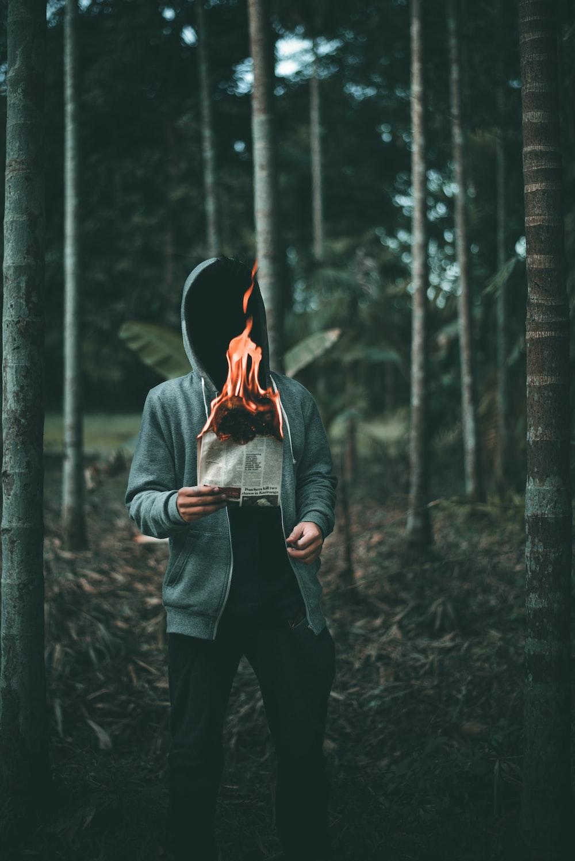 man holding burning paper near trees