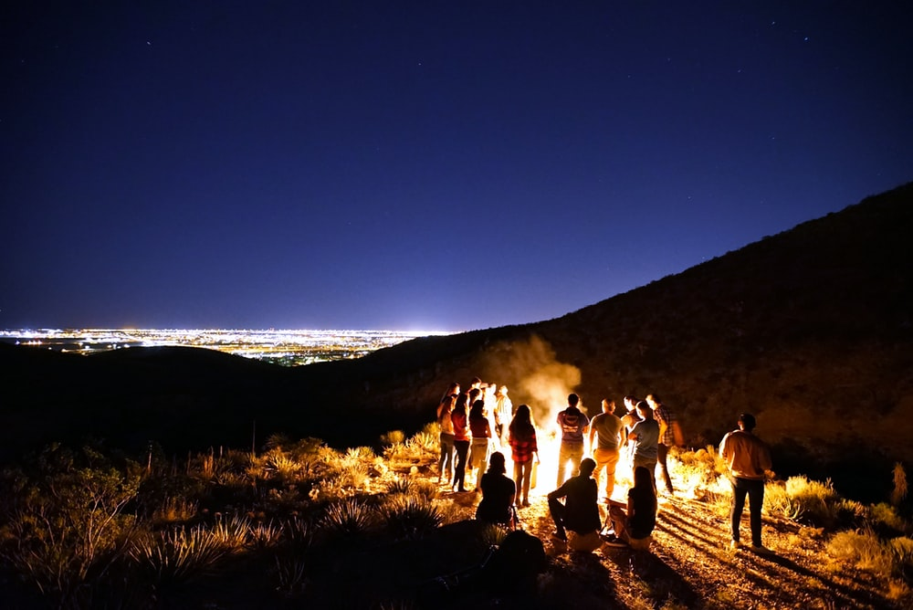 people standing in front of bon fire during nighttime