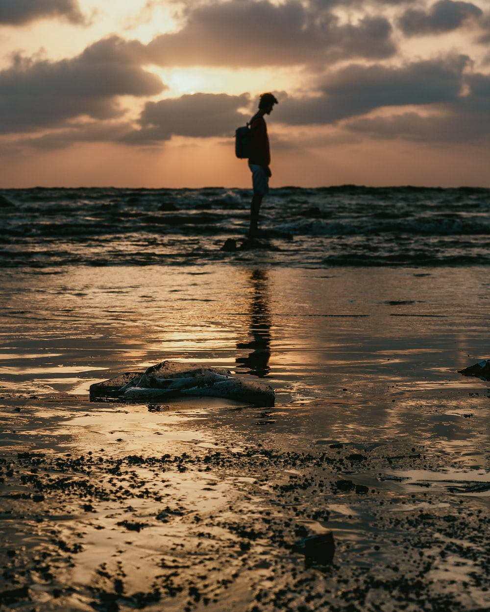 man standing on stone at the beach