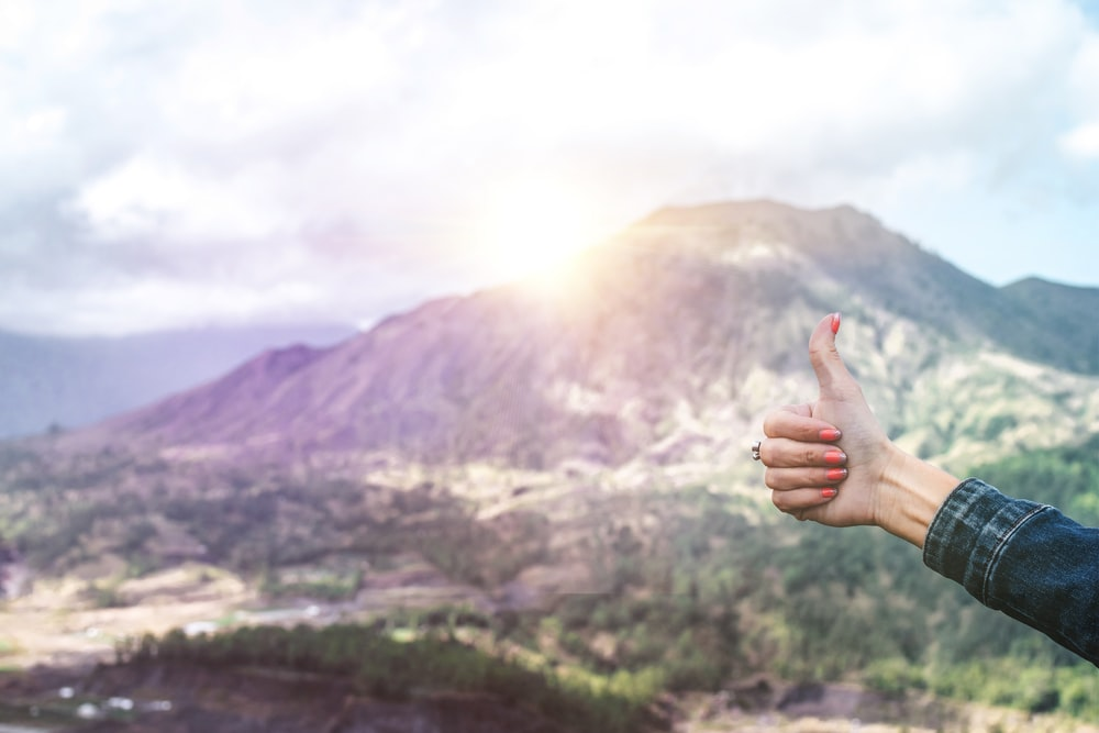 human showing hand on top of mountain