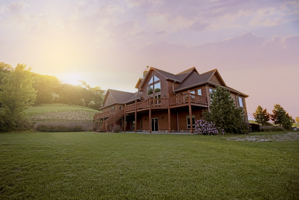 brown wooden house with green grass field