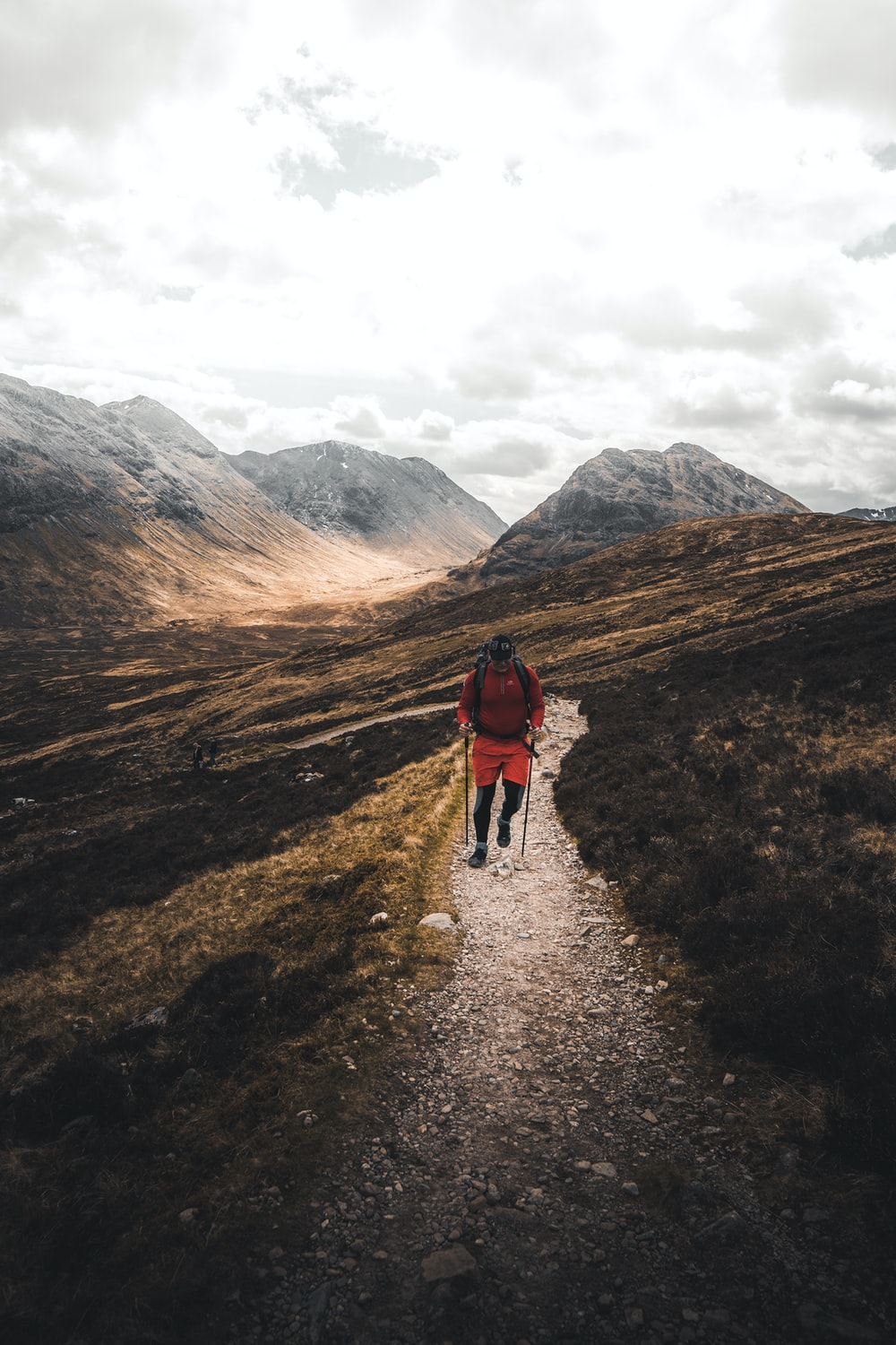 man walking on road under dramatic clouds