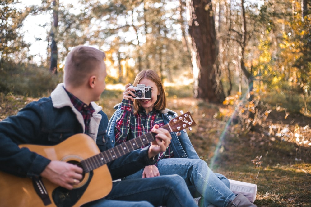 woman taking picture of man playing guitar