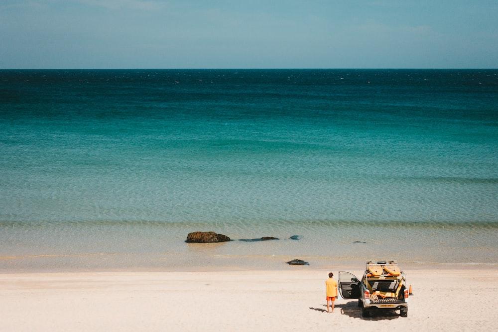 man standing near vehicle beside seashore viewing calm sea