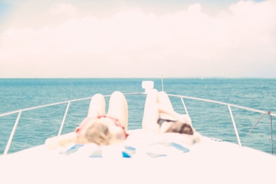 two women lying in front of the yacht under the heat of the sun
