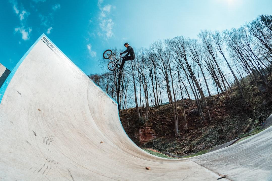 BMX Pro rider Michel Beran doing a tail whip 180 in skatepark.