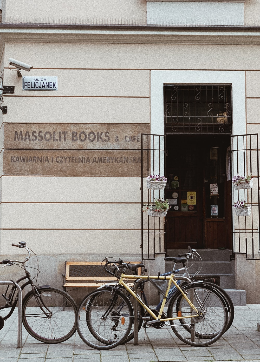 yellow bicycle parked in front of Massolit Books & Cafe