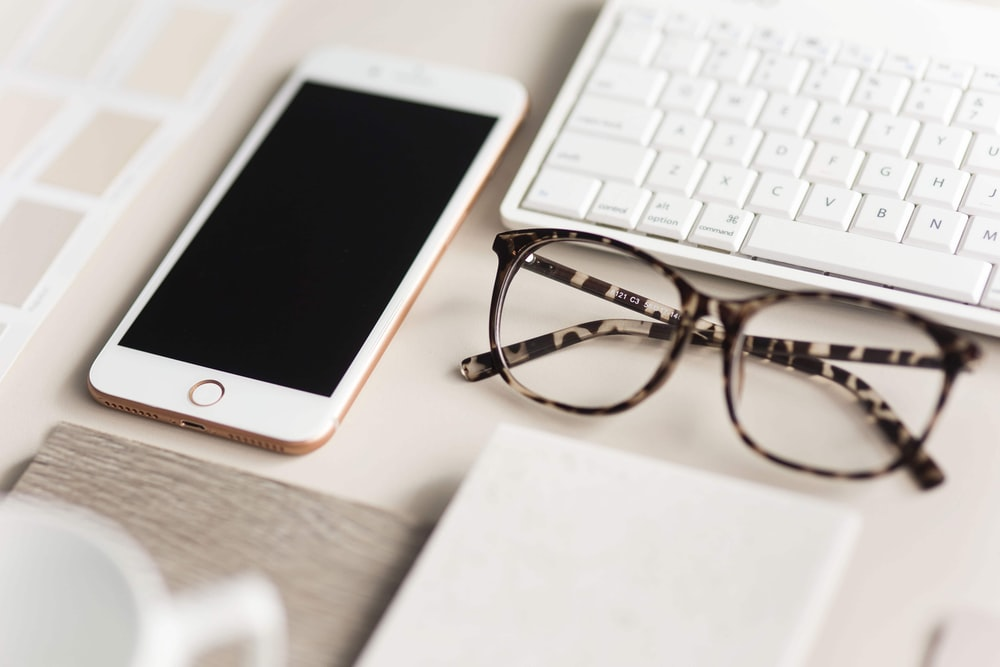 gold iPhone 7 beside black and brown framed eyeglasses