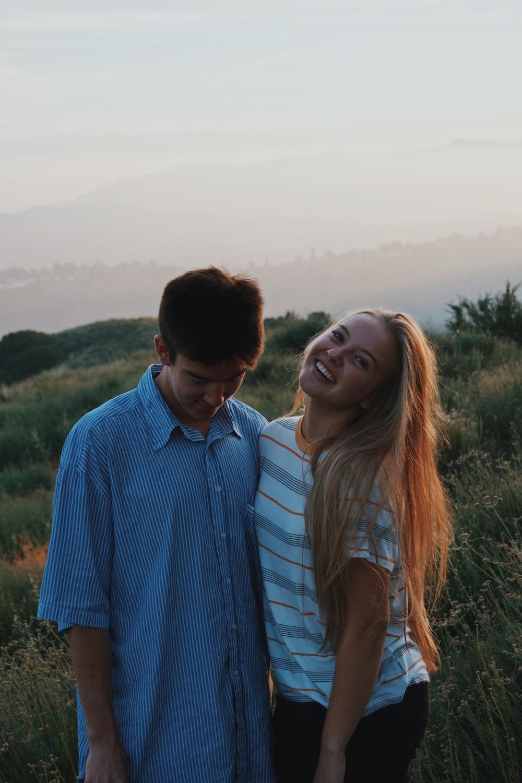 man wearing blue dress shirt and woman wearing white and gray stripe shirt standing on grassland
