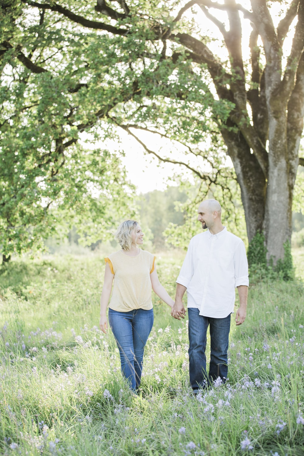 man and woman holding hands near tree