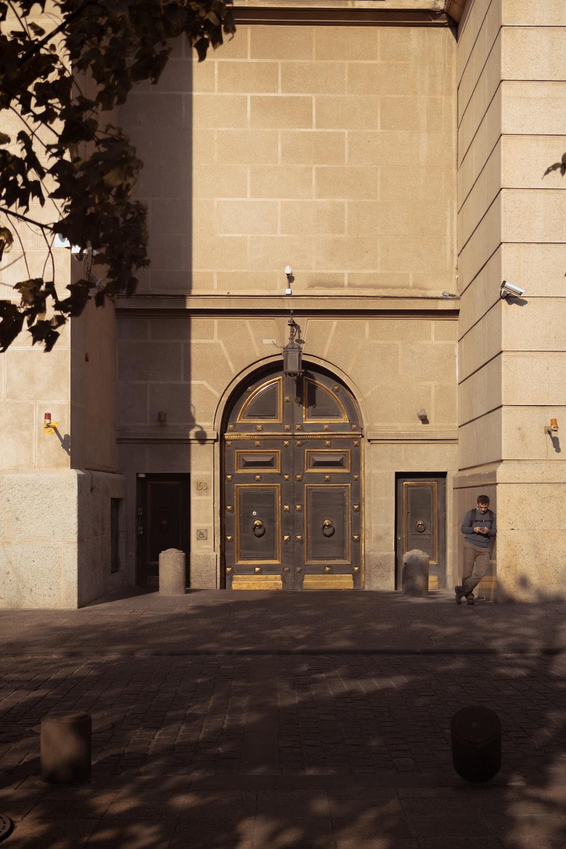 person standing near brown wooden double door
