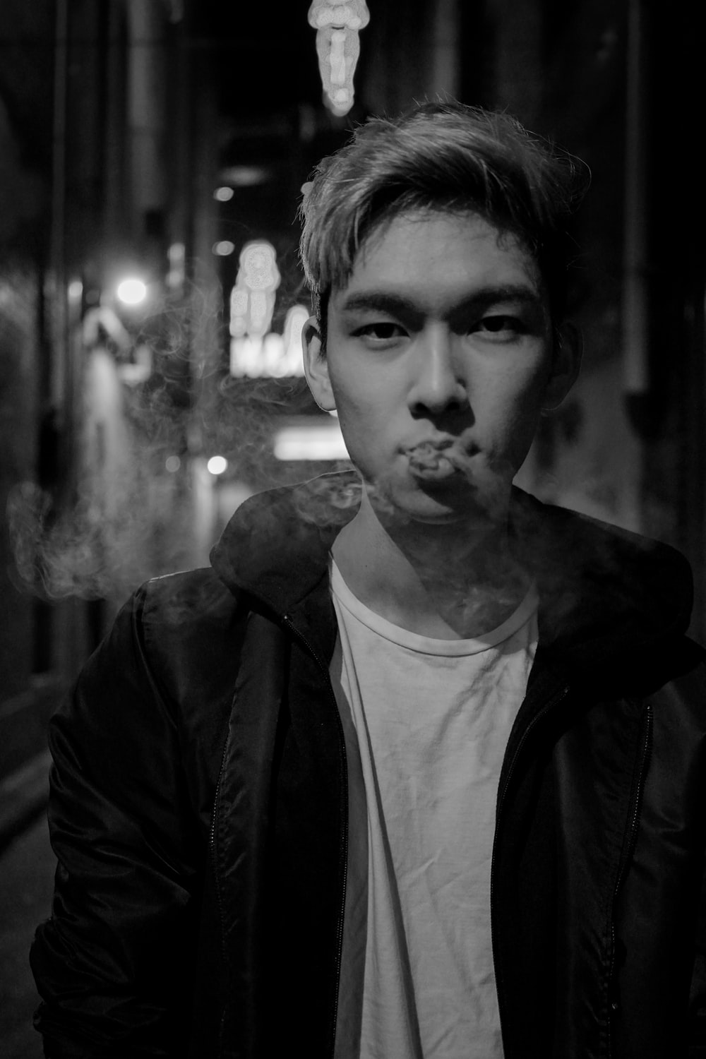 man in black jacket and white top smoking cigarette