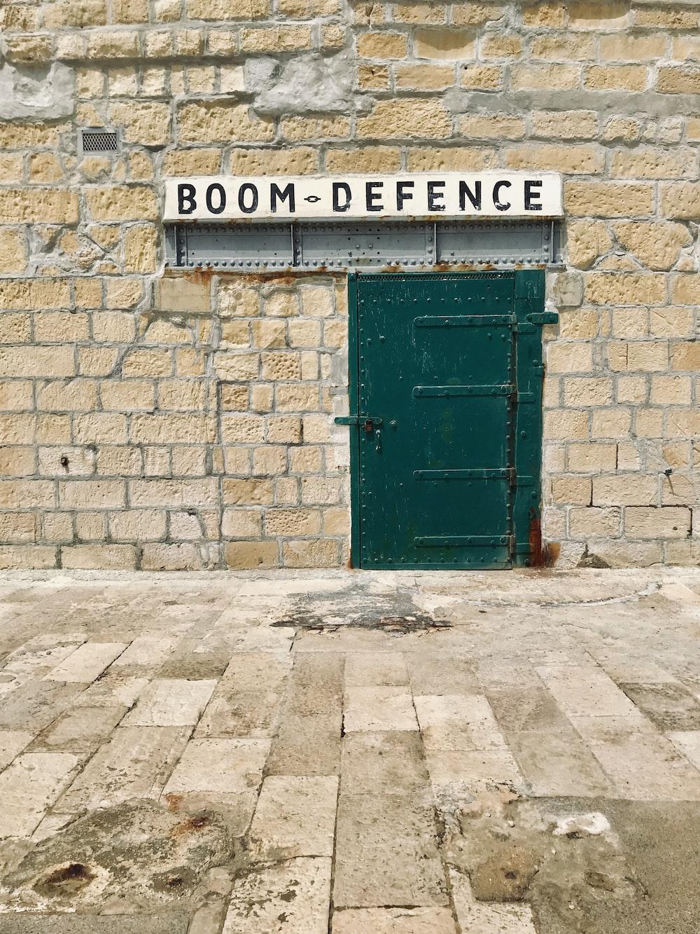 green steel door and Boom Defence signage