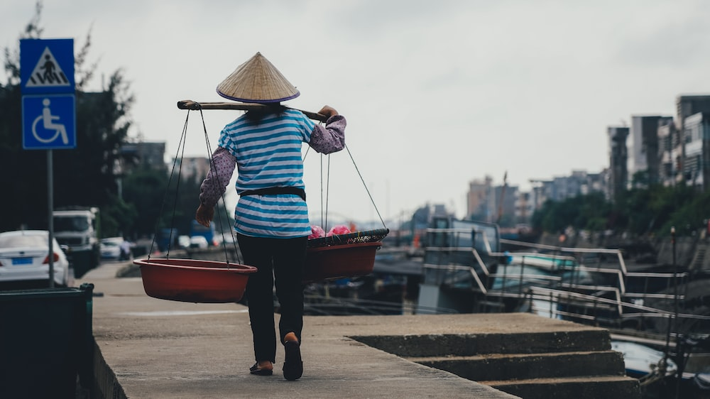 woman carrying red basins