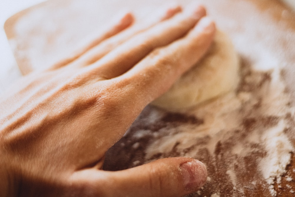 person holding white dough