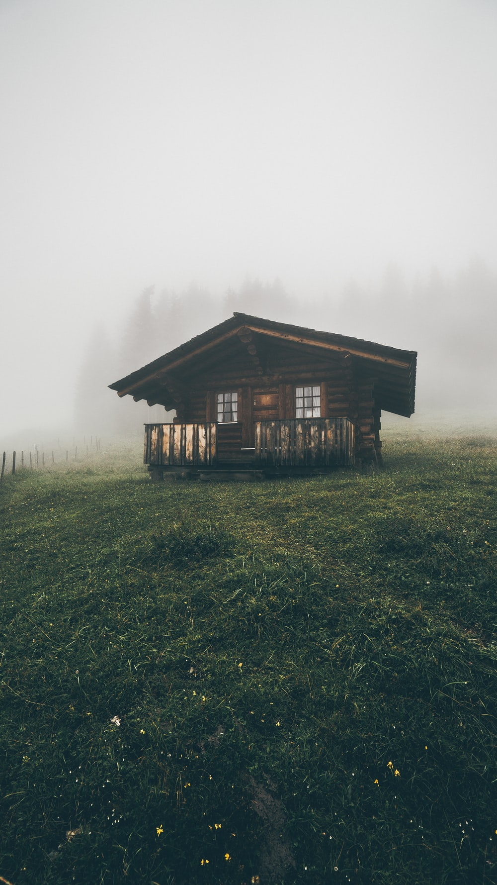 brown wooden house in a field with fog during daytime