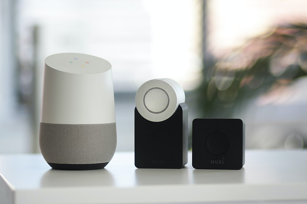white and gray Google smart speaker and two black speakers