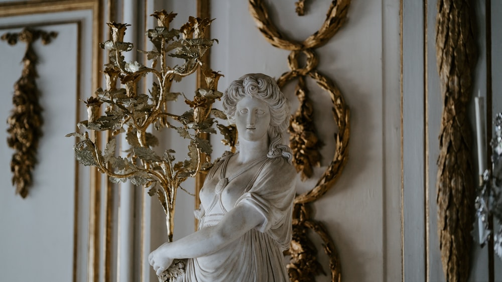 white statue carrying golden candle stand