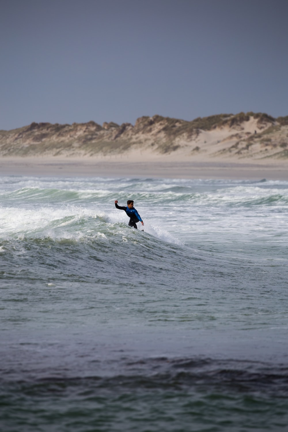 surfer riding the waves under grey sky
