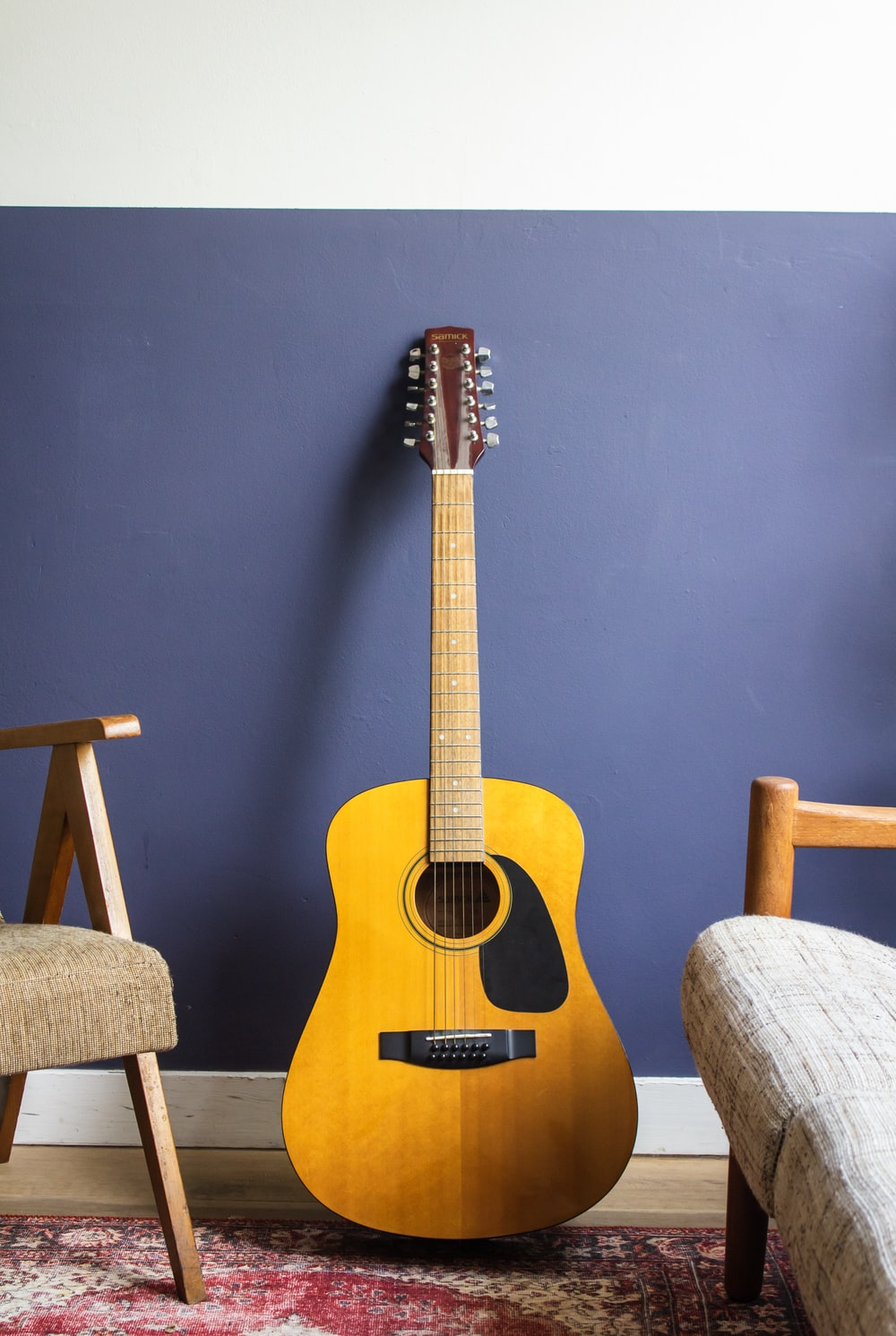 yellow acoustic guitar leaning on wall