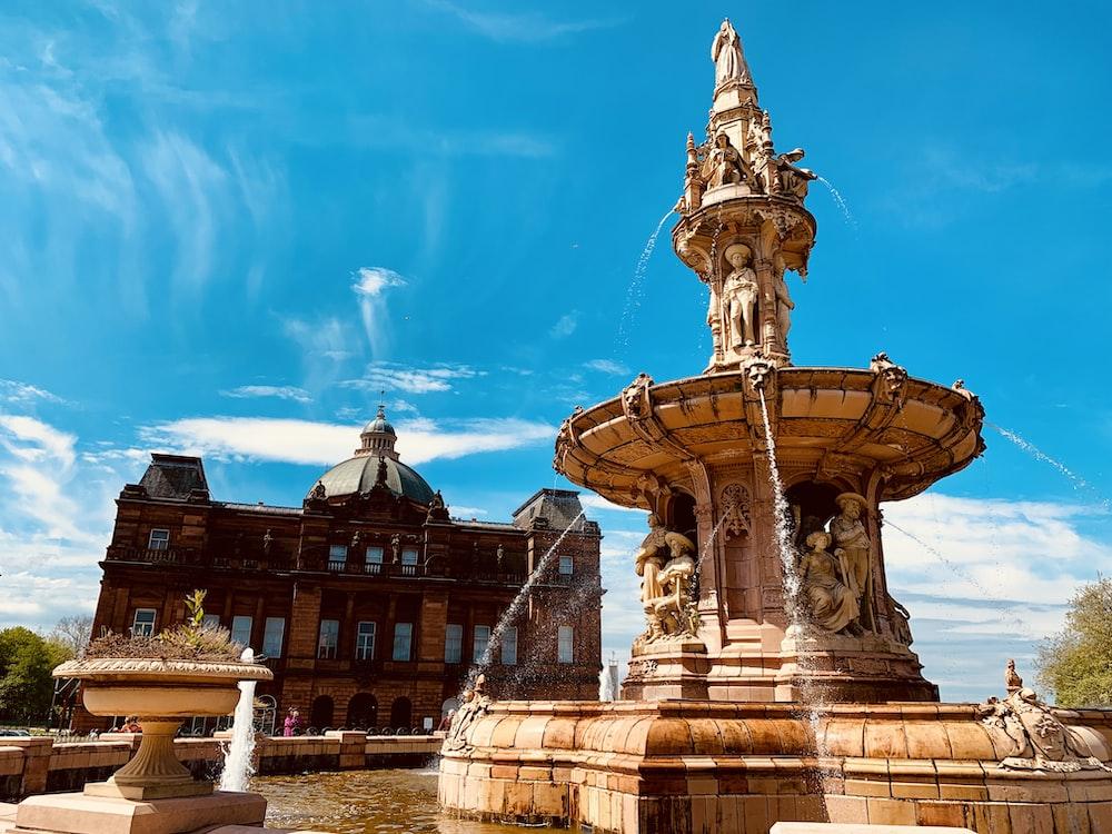 water fountain outside castle under blue sky