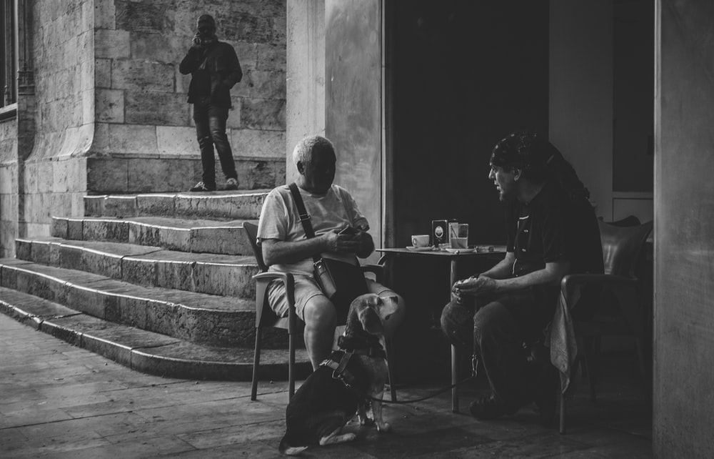 two men sitting outside building in grayscale photo