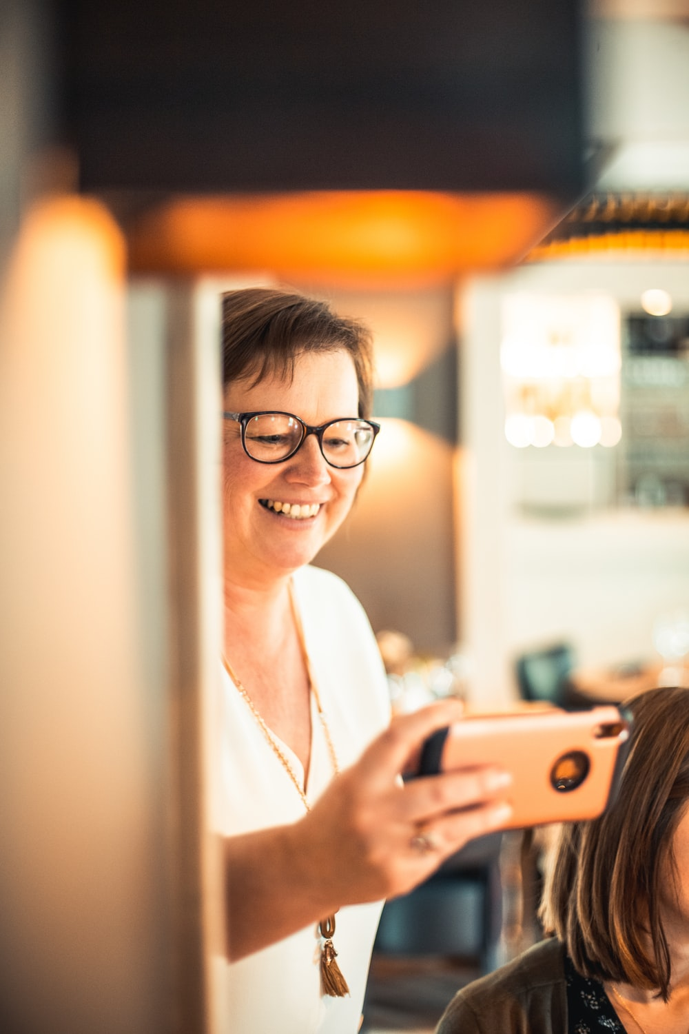 shallow focus photo of woman in white V-neck shirt using iPhone