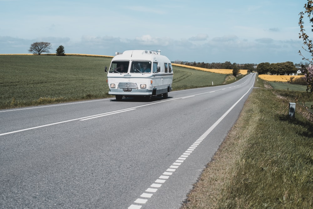 white and gray bus on gray pavement road