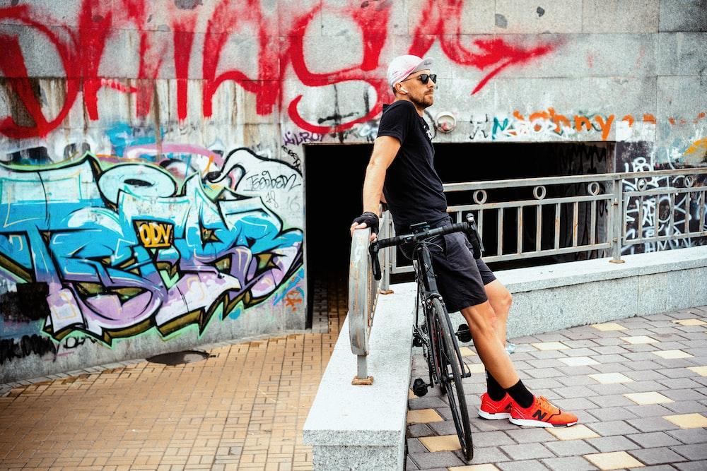 man sitting on black road bike