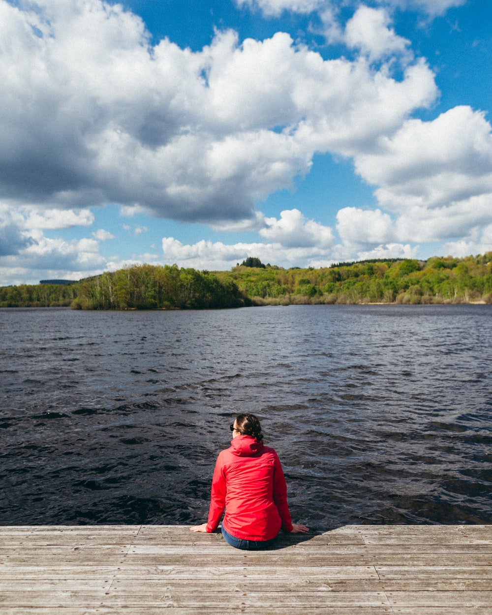 woman wearing red hoodie sitting in front of body of water