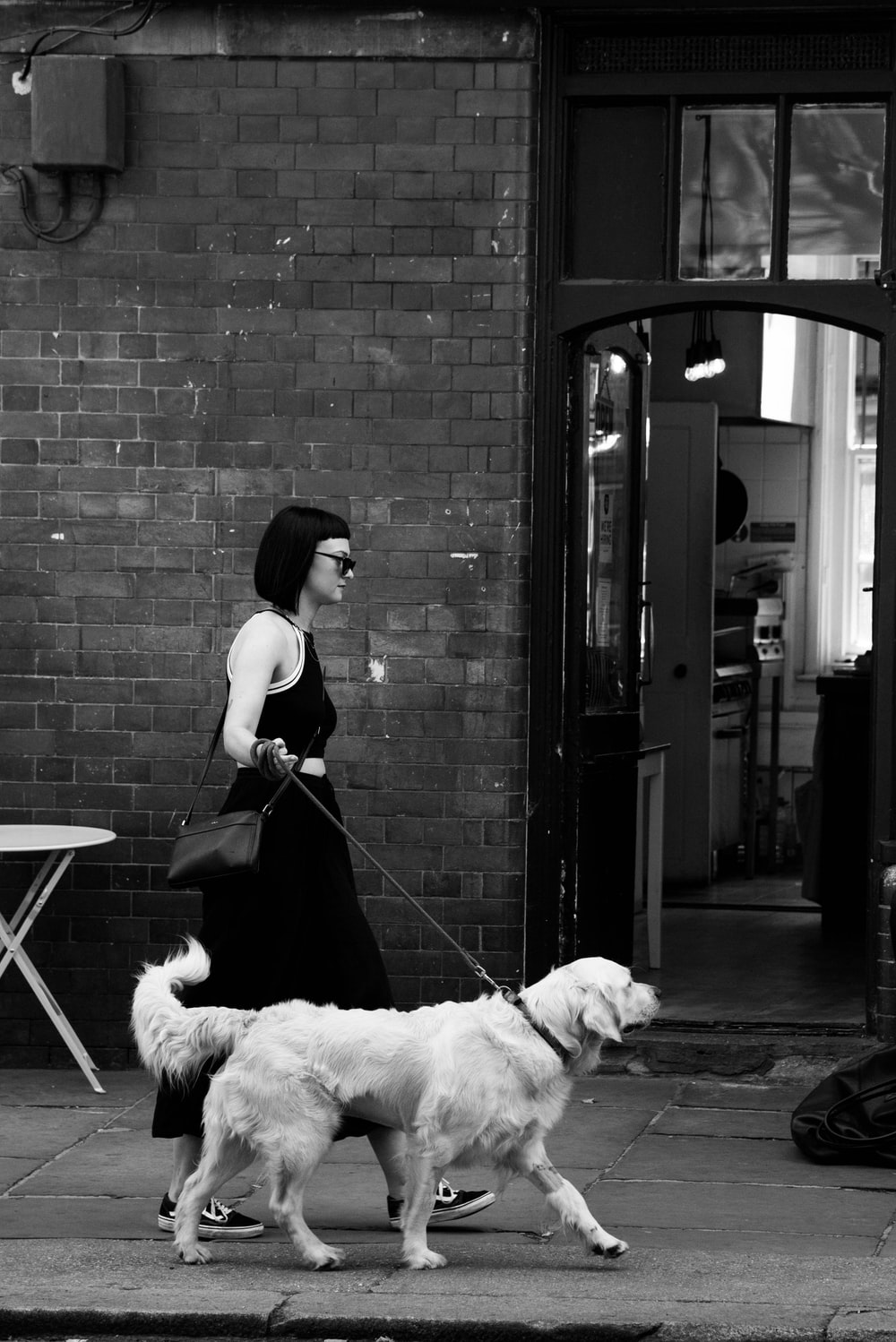 grayscale photo of woman walking with dog