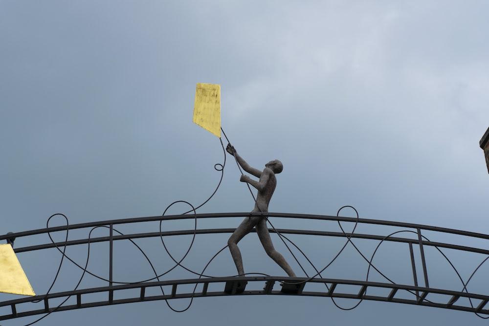 man holding kite statue