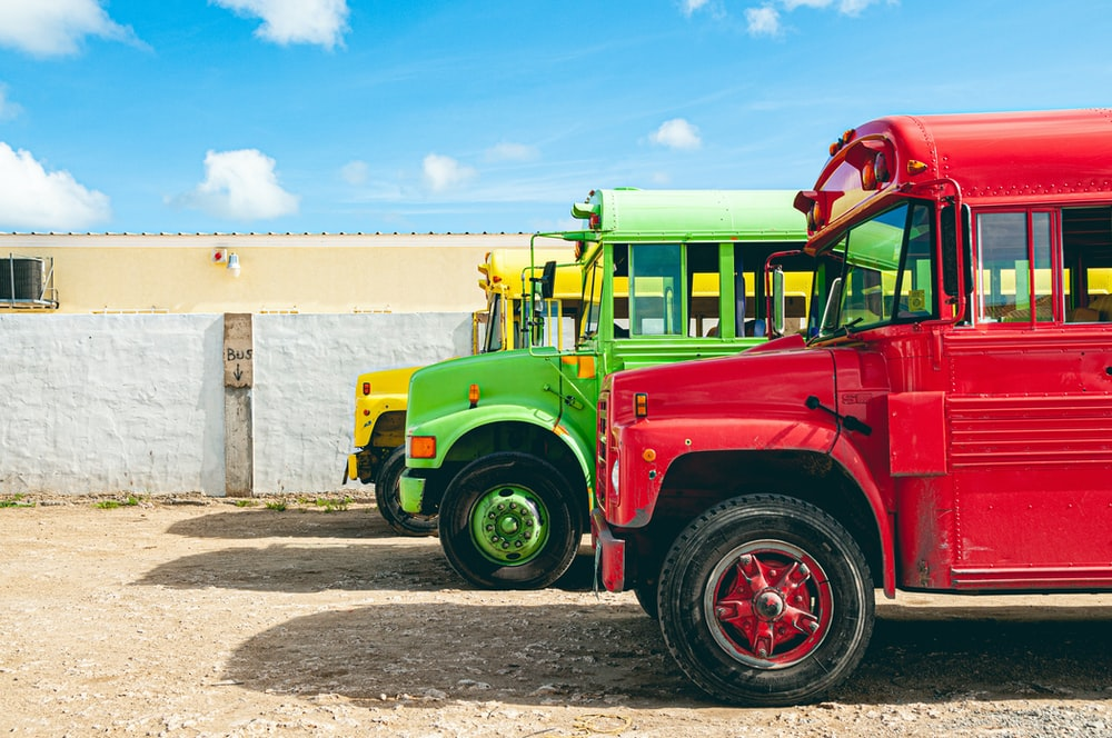 yellow, green, and red trucks parked on road at daytime