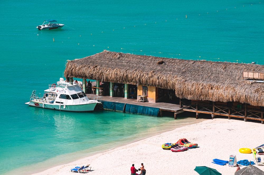 white motor boat beside hut