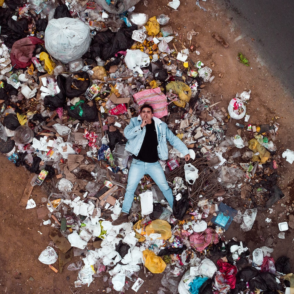 man lying on garbage pile in aerial photography
